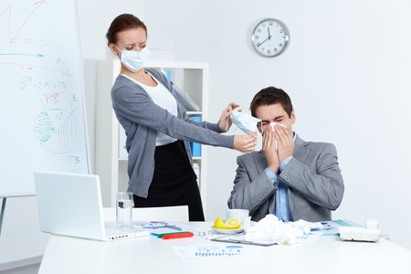 infect: Image of businessman sneezing while his partner in mask offering him to put on one in office