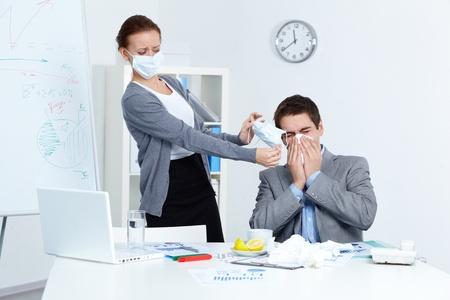 sneezing: Immagine di starnuti uomo d'affari, mentre il suo partner in maschera che gli offriva di mettere su uno in ufficio Archivio Fotografico
