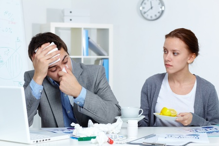 healthcare worker: Image of sick businessman and his secretary giving him a cup of tea and lemon in office  Stock Photo