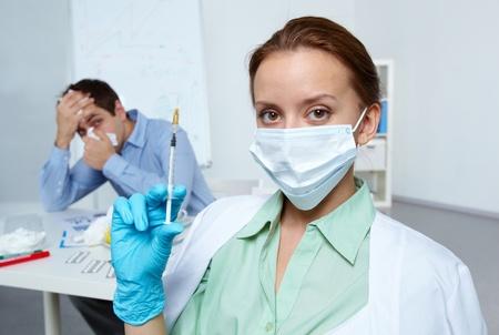 Image of businessman sneezing with nurse holding syringe on background photo