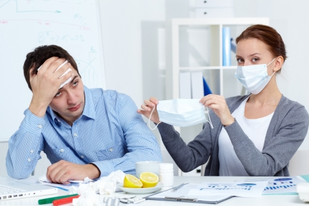 Image of businessman sneezing while his partner in mask offering him to put on one in office  photo