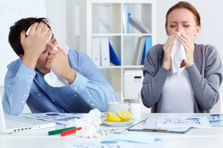 cold virus: Image of sick business partners blowing their noses in office  Stock Photo