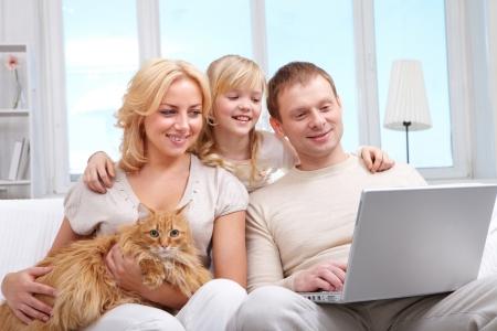 Una familia de tres con el gato sentado en el sofá y mirando la pantalla del portátil