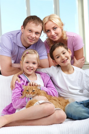 sibling: A young family of four with a cat sitting on sofa, looking at camera and smiling