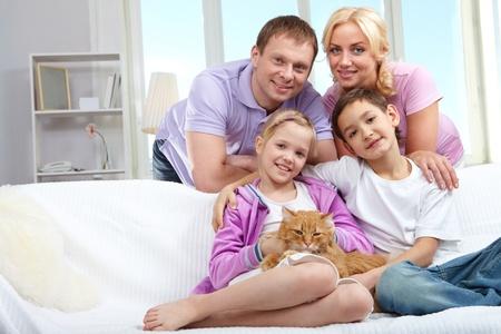 Una joven familia de cuatro miembros con un gato sentado en el sofá, mirando a cámara y sonriendo