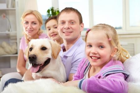 Una familia feliz de cuatro personas con un perro sentado en el sofá, la atención se centra en la hija