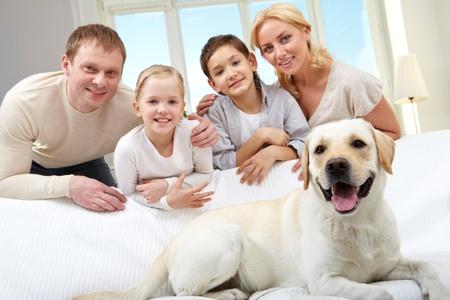 familia abrazo: Un gran perro acostado en el sof�, una familia de cuatro personas de pie detr�s de