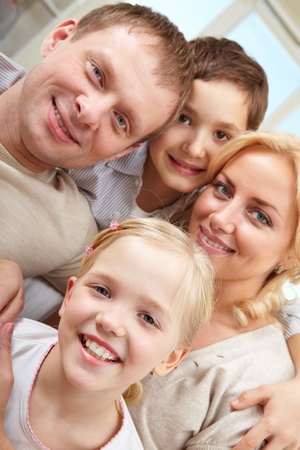 Close-up of a smiling family of four looking at camera Stock Photo - 11425795