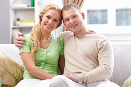 Happy couple sitting on sofa and looking at camera  photo