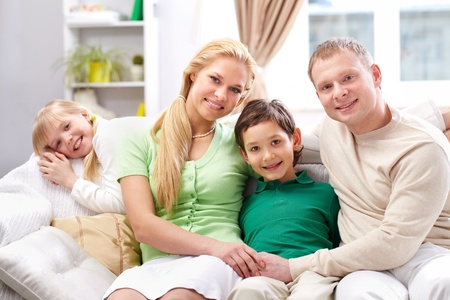 four person: A young family of four sitting on sofa, looking at camera and smiling Stock Photo