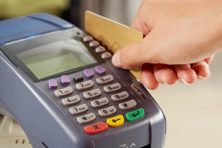 keeping: Close-up of payment machine while human hand keeping plastic card in it