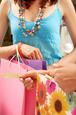 Close-up of woman�s hand holding credit card and bags with another female near by during shopping in the mall photo