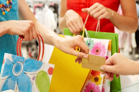 passing over: Close-up of woman�s hand passing over credit card to shop assistant on background of another female Stock Photo