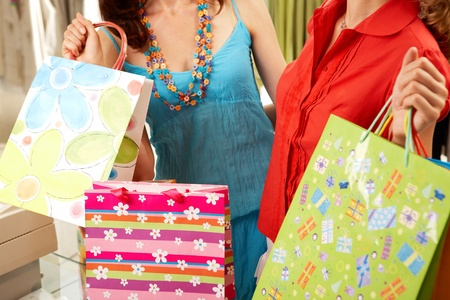 Close-up of two girls carrying shopping bags in the mall photo