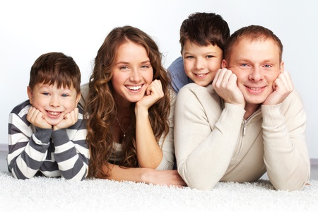 A young family of father, mother and two kids posing in front of camera photo