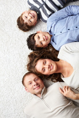 A young family lying on the floor and looking at camera photo