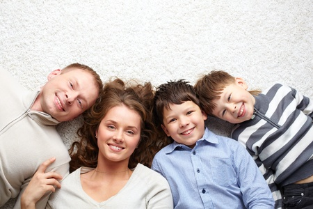 four person: A young family of father, mother and two kids looking at camera
