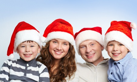 Portrait of four happy family members in Santa caps looking at camera with smiles Stock Photo - 11425914