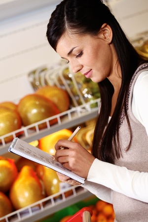 Image of pretty woman ticking what she has bought in supermarket Stock Photo - 11425904