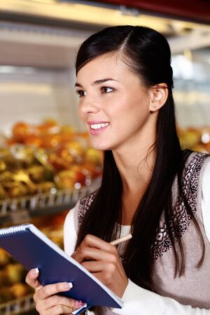 interested: Image of pretty woman with notepad looking somewhere in supermarket Stock Photo
