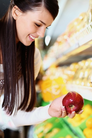Image of happy woman with fresh apple in hand looking at it in supermarket Stock Photo - 11425878