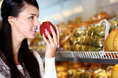Image of young woman with fresh apple in hand smelling it in supermarket Stock Photo - 11425876