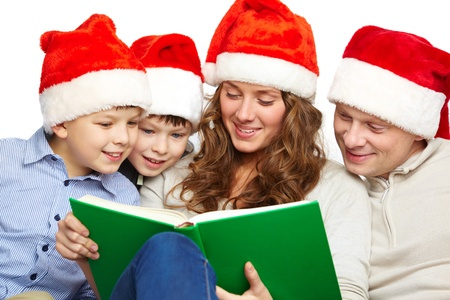 Portrait of four happy family members in Santa caps reading book photo