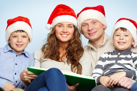 Portrait of four happy family members in Santa caps looking at camera Stock Photo - 11425926