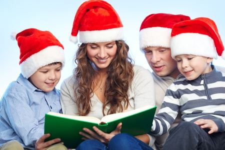 Portrait of four happy family members in Santa caps reading book Stock Photo - 11425928