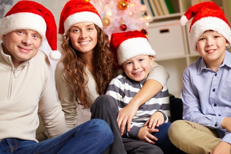 Portrait of four happy family members in Santa caps looking at camera at home photo