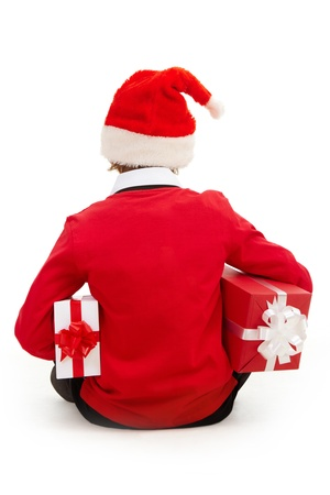 Rear view of boy in Santa cap with giftboxes photo