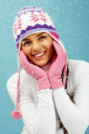 Portrait of pretty woman in pink gloves and knitted winter cap looking at camera with smile photo