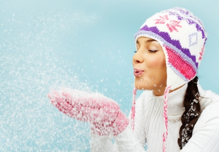 snow girl: Image of pretty woman in pink gloves and knitted winter cap blowing snow from her palms