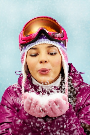 Portrait of a girl blowing snow out of hands against blue background photo
