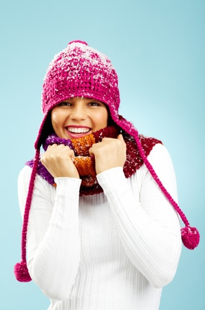 Portrait of pretty woman in knitted winter cap and scarf looking at camera with smile photo
