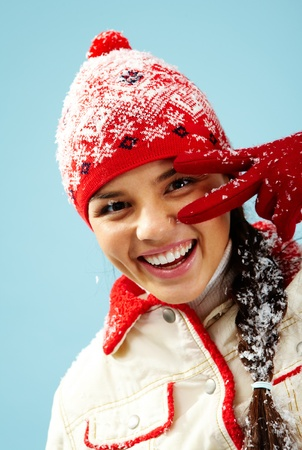 Face of pretty woman in gloves and knitted winter cap looking at camera with two fingers by her eye photo