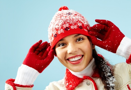 Pretty woman in red gloves and knitted winter cap looking at camera with astonishment photo