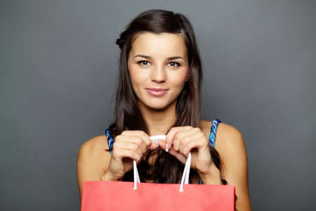 Portrait of happy brunette with paperbag looking at camera Stock Photo - 11448516
