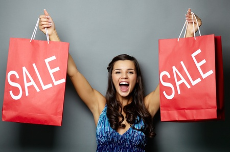 happy shopper: Portrait of joyful brunette with sale paperbags looking at camera