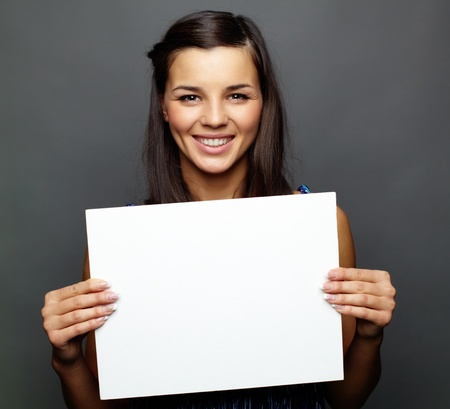 hand holding paper: Portrait of happy brunette with advert looking at camera Stock Photo