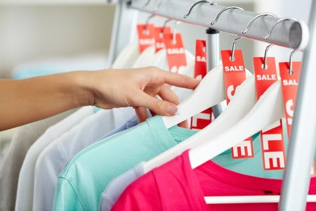 Photo of human hands searching through hangers with clothes photo