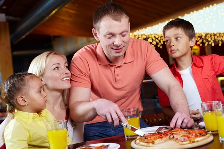 Portrait of cute children and their parents in pizzeria photo
