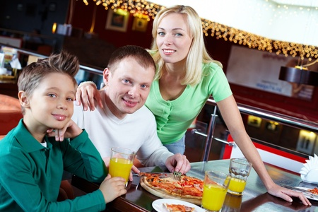 a little dinner: Portrait of happy family of three in pizzeria