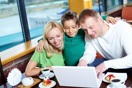 Image of happy family looking at laptop screen in cafe Stock Photo - 11448534