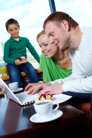 Image of happy family looking at laptop screen in cafe photo