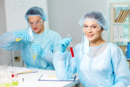Confident clinician studying new substance in laboratory with her colleague on background photo