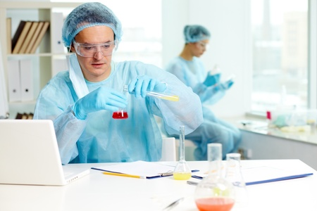 Confident clinician studying new substance in laboratory with his colleague on background photo