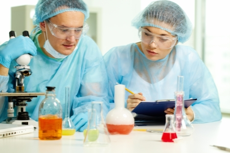 chemical substance: Serious chemists making experiment with new substance in laboratory