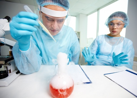 Laboratory worker is about to inject fluid into chemical substance during experiment  photo