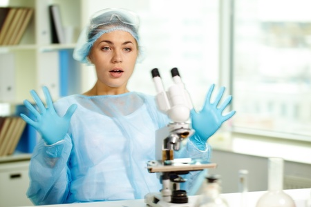 clinician: Surprised clinician looking at microscope in laboratory Stock Photo